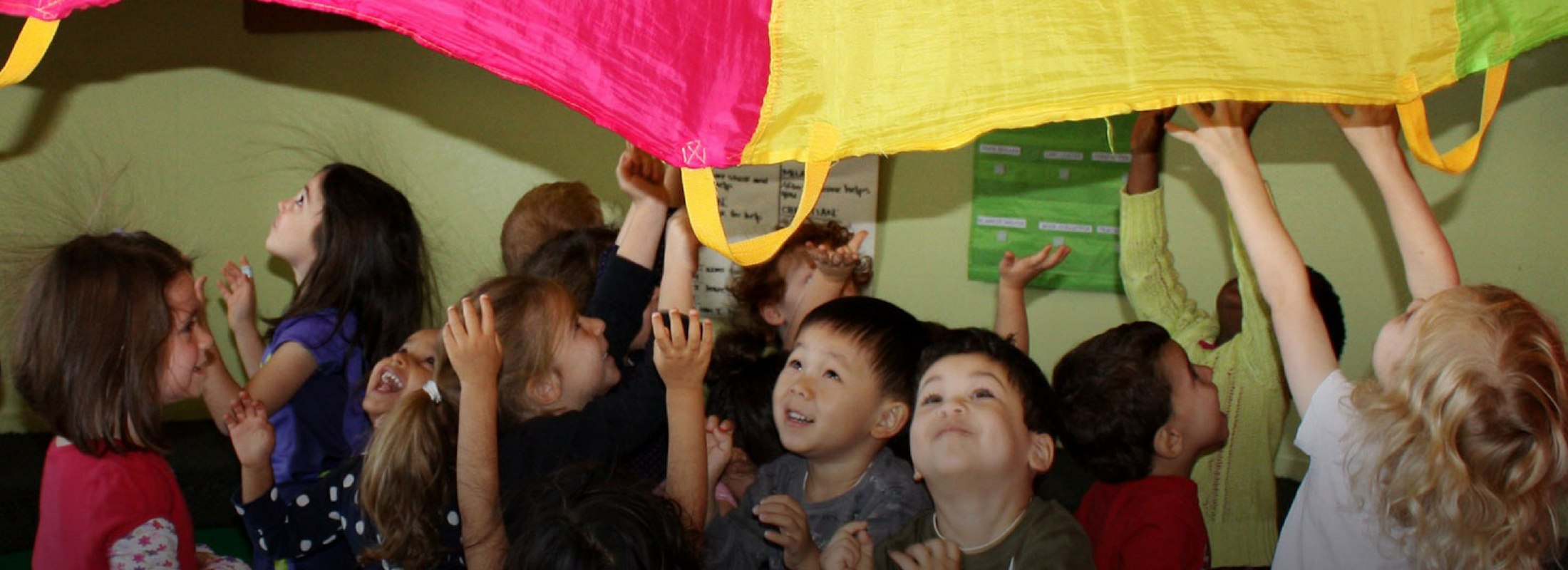 A group of preschool-aged children playing with a parachute