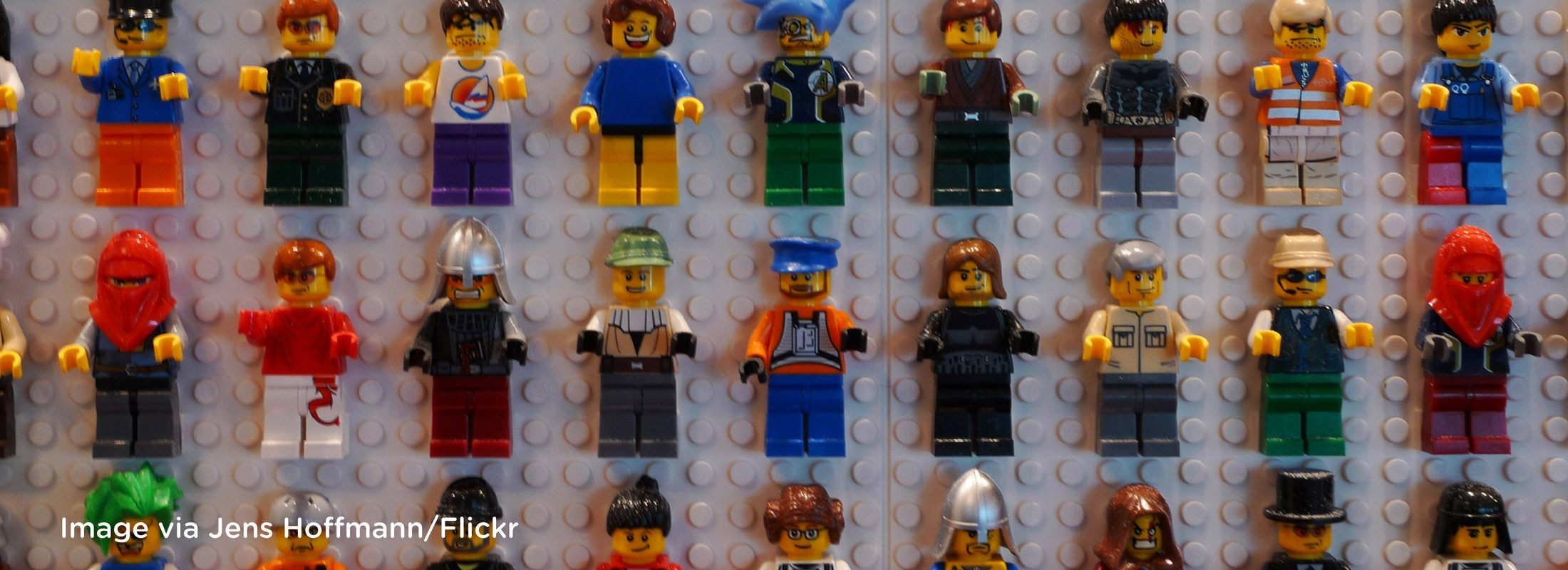 Different kinds of Lego people lined up in rows on a grey surface