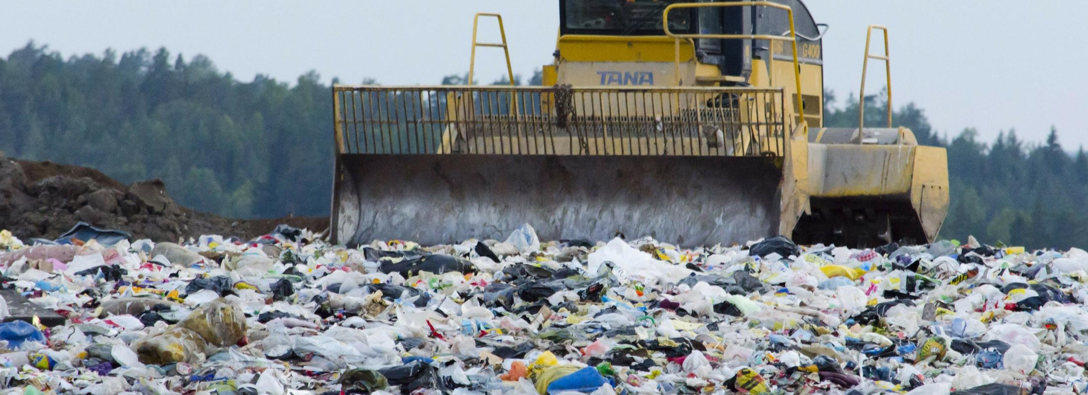 A bulldozer at a landfill pushing around trash